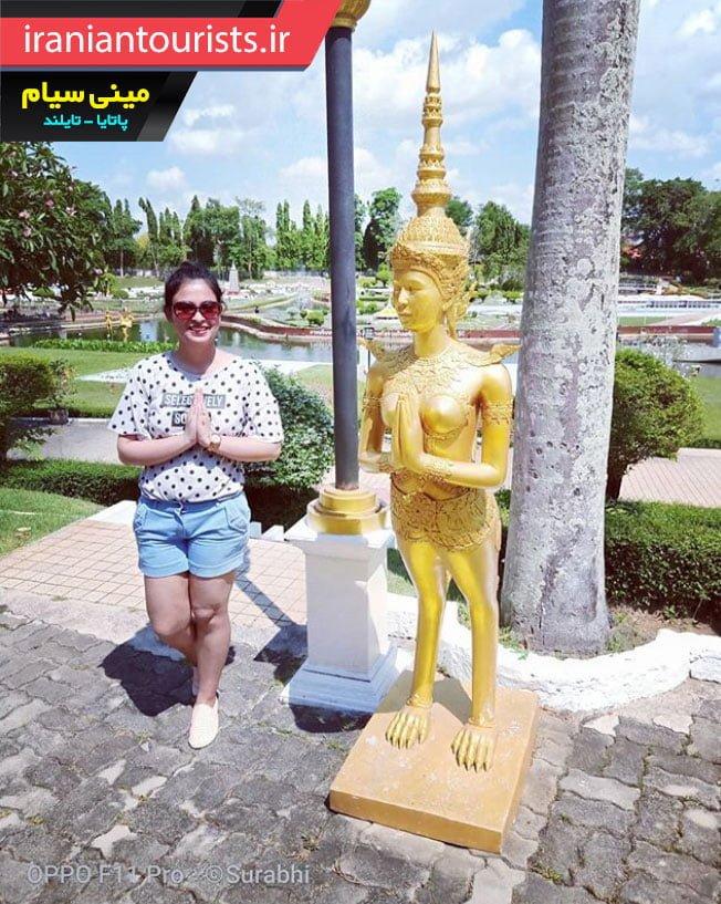 زن گردشگر در کنار مجسمه طلایی در مینی سیام شهر پاتایا