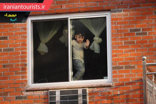 نمایی از کودکی در پشت پنجره خانه ای در نیویورک در دوران قرنطینه